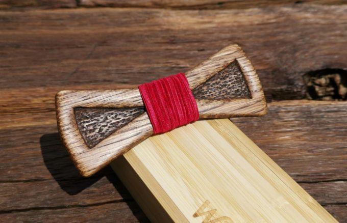 Holzfliege mit rotem Seidenband auf Holzkiste