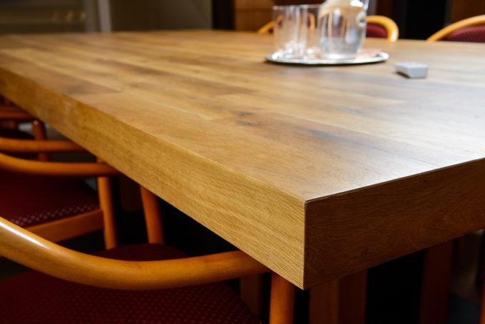 Holztisch in Seminarraum mit Fernbedienung, Wasserkrug und Glas, mit Stühlen
