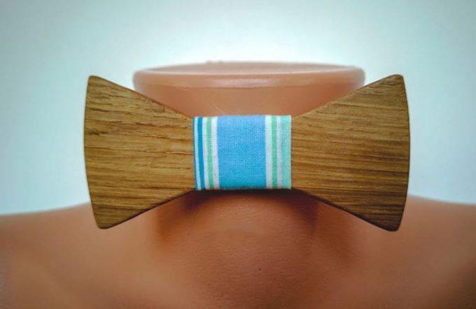 Holzfliege mit blaugestreiften Seidenband auf Puppe