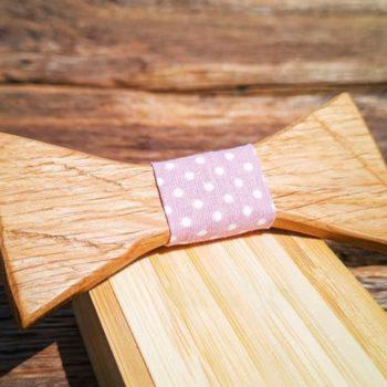 Fliege aus Holz mit violettem, gepunktetem Band aus Seide, liegend auf Holzschachtel