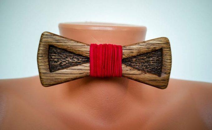 Holzfliege mit rotem Seidenband auf Puppe