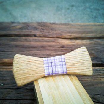 Fliege aus Holz mit violett kariertem Seidenband, auf Holzkiste liegend