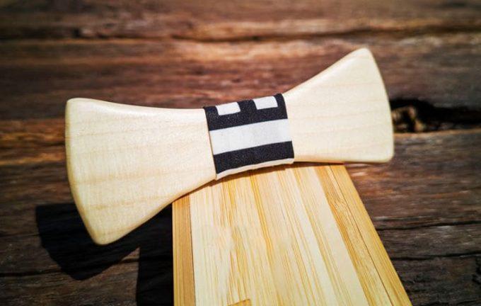 Holzfliege mit Seidenband, schwarz-weiß gemustert, liegend auf Holzkiste