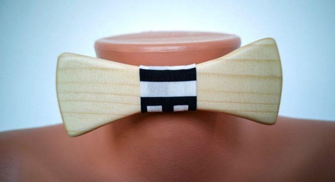 Fliege aus Holz mit Seidenband, schwarz-weiß gemustert, auf Puppe angebracht