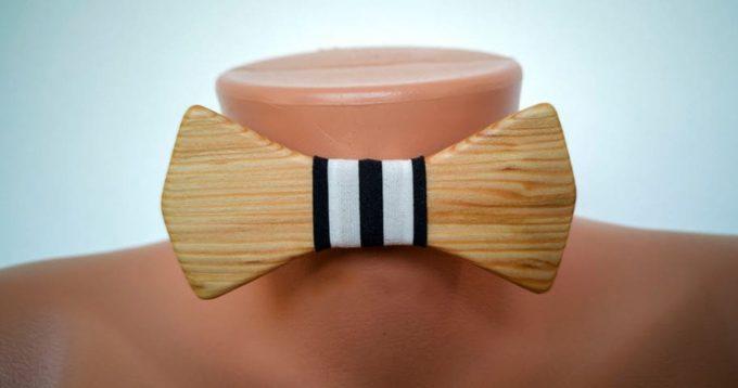 Fliege aus Holz mit Seidenband, schwarz-weiß vertikal gestreift. Auf Puppe angebracht