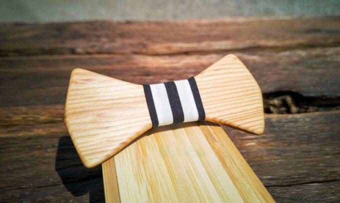 Fliege aus Holz mit schwarz-weiß gestreiftem Seidenband, vertikal gestreift. Fliege liegt auf Holzkiste als Verpackung