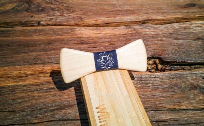 Fliege aus Holz von der Tischlerei Wilmont GmbH, mit Seidenband in Blattmuster, auf Holzschachtel liegend