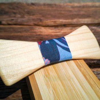 Fliege aus Holz mit Seidenband in blauem Muster, auf Holzkiste liegend