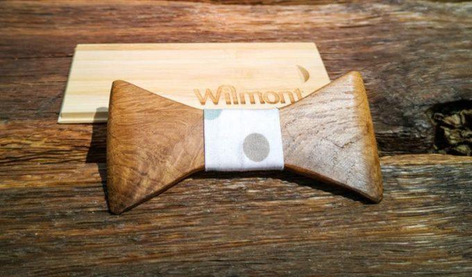Holzfliege auf Tisch an Holzkiste gelehnt, mit Seidenband in gepunktetem Muster
