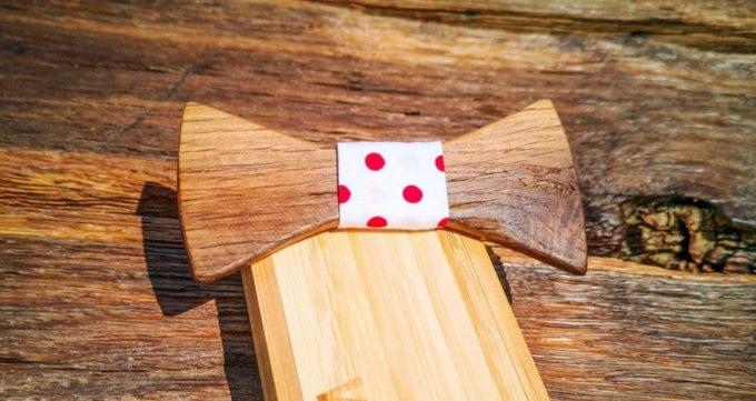 Holzfliege im angesagten Retrostyle mit roten Punkten am Seidenband. Fliege liegt auf Holzkiste, diese ist die Verpackung