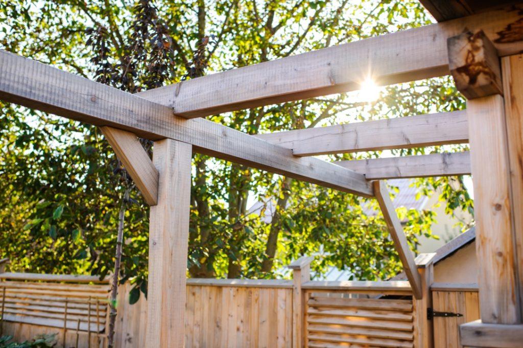 Terrassenüberdachung mit Sonnenschein und Bäumen im Hintergrund in Telfs