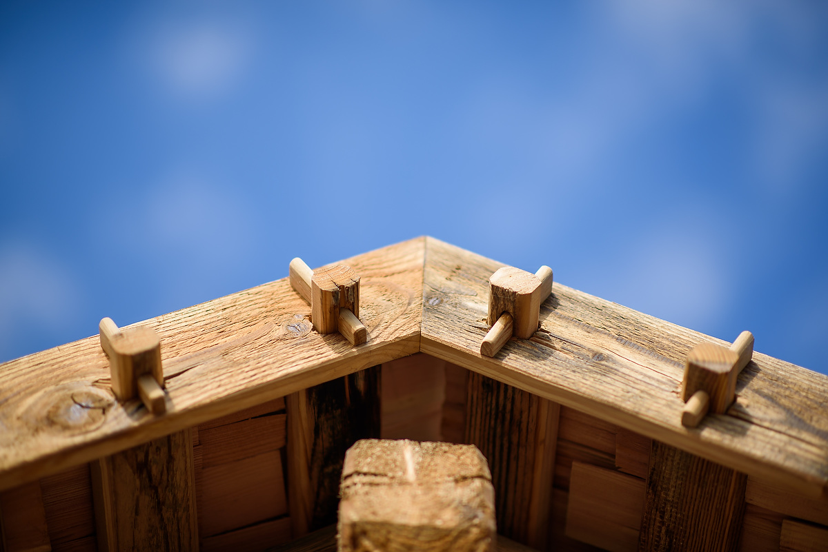 Vordach aus Altholz mit blauem Himmel im Hintergrund