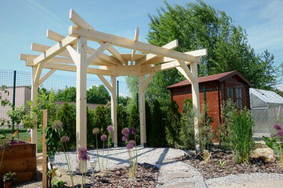 Pergola im Garten mit Gartenhaus im Hintergrund