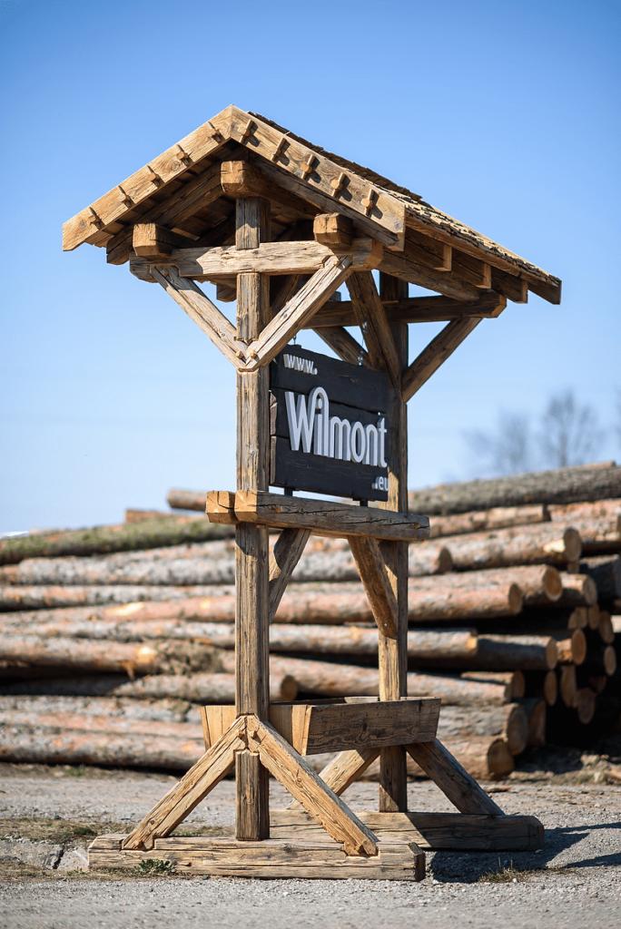 Firmenschild mit Logo auf Holzständer mit Baumstämmen im Hintergrund