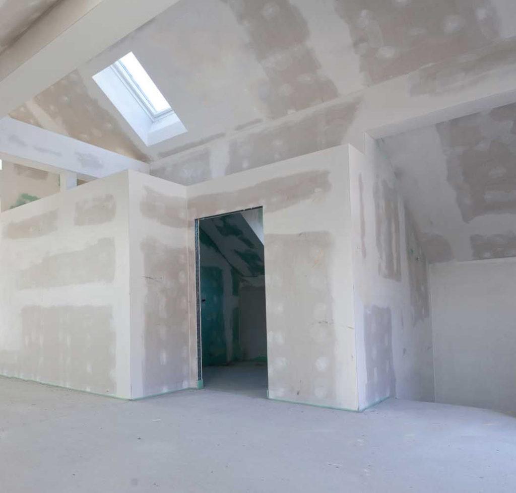 Trockenbau in Tirol mit der Wilmont GmbH aus Telfs. Ein Fenster ist sichtbar und ein offener Bereich für die Türe. Wände sind verputzt.