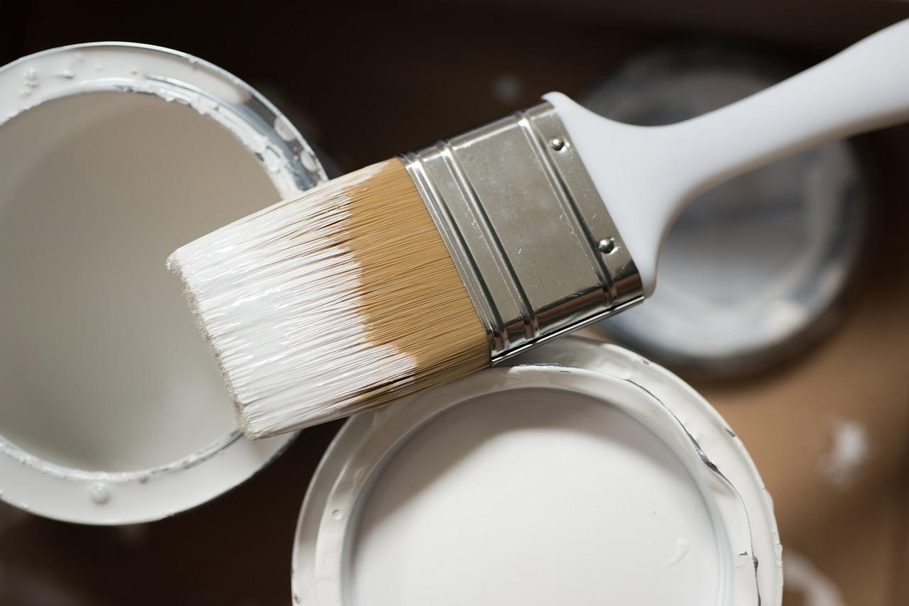 Pinsel und weiße Wandfarbe für Wohnungssanierung in Tirol